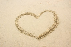 Drawn heart shape on sand Stock Images