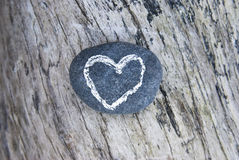 Drawn heart on stone lying on wood Royalty Free Stock Images