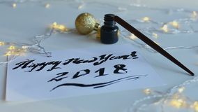 Drawn inscription Happy New Year 2018. Calligraphy card for New Year 2018. Broad nib pen, black ink and twinkling garlands. Concept of holiday art inspiration stock video footage