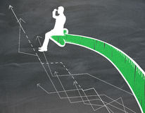 Drawn man on green arrow. Drawn man sitting on green chart arrow and looking into the distance on chalkboard background Royalty Free Stock Photos