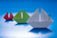 Drawn man looking through spyglass on Paper Boat Sailing with other on Blue paper sea with Drawn Details. Origami Ship. Drawn captain looking through spyglass on royalty free stock photo