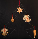 The drawn New Year tree with straw jewelry. On a black board chalk has drawn a fir-tree, Christmas tree decorations from straw are attached to the drawing Royalty Free Stock Photos