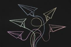 Drawn paper planes with route trace on chalkboard background. Choose your own way. Colorful drawn paper planes with route traces on chalkboard background, copy stock images