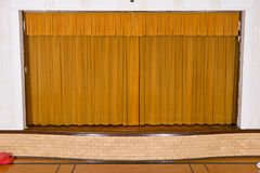 Drawn curtains on small school assembly stage stock image