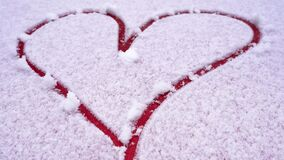 Drawn romantic heart shape on snow. Painted red heart on the snow-covered hood of the car. Bonnet of the automobile in