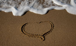 Drawn in the sand heart with the oncoming wave Royalty Free Stock Photos
