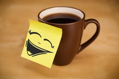 Post-it note with smiley face sticked on cup Royalty Free Stock Image