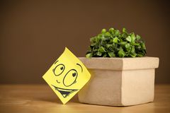 Post-it note with smiley face sticked on flowerpot Stock Photography