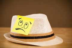 Post-it note with smiley face sticked on hat Stock Images