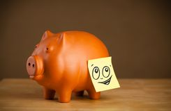 Post-it note with smiley face sticked on piggy bank Stock Images