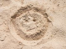 Drawn smiley face in summer beach sand. Painted head in dray salt sand. Stock Photos