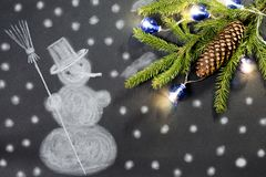 Painted snowman and fir branch with decorations on black background Royalty Free Stock Image