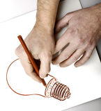 Drawnng hands. Hands drawing a bulb lamp Royalty Free Stock Photos