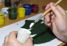 Draws green tree gouache, scoops the paint from the jar with a b Stock Photos