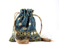 Drawstring Purse. Decorative drawstring pouch in Indian textile, embroidered in gold silk and with mirrors and golden tassels. Isolated on a white background Stock Photos