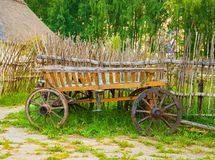 Dray. Old wooden cart on the lawn near the fence Royalty Free Stock Photo