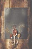 Dray pikantność na metal łyżce na czerń kamieniu Drewniany tło C zdjęcia royalty free