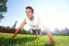 Drücken Sie den Mann hoch, der Liegestütze im Central Park New York tut Stockfotos