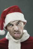 Dreadful Santa. Portrait of man in Santa costume making dreadful faces at camera Royalty Free Stock Photography