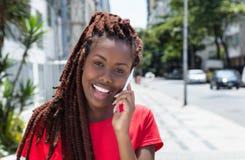 有dreadlocks的非洲妇女讲话在电话在城市 免版税图库摄影