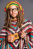 Dreadlocks man. Portrait of a hippie young man playing his guitar royalty free stock images