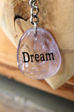 Dream. Pink dream key chain against a wooden background Royalty Free Stock Images