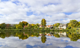 Dream autumn village and its reflection Stock Photos