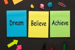 Dream Believe Achieve. Words written on color notes and office supplies on black background. Motivational quote stock photo