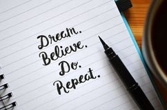 DREAM. BELIEVE. DO. REPEAT. hand-lettered in notebook. On lined paper with brush pen and cup of coffee on wooden desk royalty free stock photo