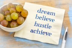 Dream, believe, hustle, achieve - text on napkin. Dream, believe, hustle, achieve - inspirational handwriting on a napkin Stock Images