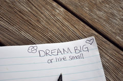 Dream Big. A notebook on a wooden deck with a ballpoint pen with doodles and Live Big or live small hand written on the corner of the page Royalty Free Stock Photography