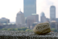 Dream big. Dream rock sits on cement ledge with the boston skyline in the background,representing dreams of success Royalty Free Stock Photography