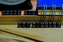Dream big act bigger written on wooden blocks. Education and business concept. On wooden background royalty free stock photography