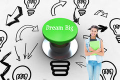 Dream big against digitally generated green push button. The word dream big and student holding notepads against digitally generated green push button Royalty Free Stock Image