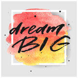 Dream big hand drawn lettering on watercolor splash on watercolor splash in red and yellow colors. Stock Photos