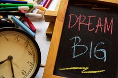 Dream big on phrase colorful handwritten on chalkboard, alarm clock with motivation and education concepts royalty free stock photography