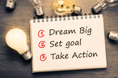 Dream Big, Set Goal, Take Action. Dream Big - Set Goal - Take Action, handwriting on notebook with light bulbs Stock Photo