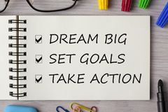 Dream Big, Set Goal, Take Action written in notebook. On wooden desk with marker pen and glasses. Top view Stock Photo