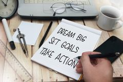Dream Big Set Goals Take Action. Words letter, written on notepad, work desk top view. Motivational business typography quotes concept royalty free stock photos