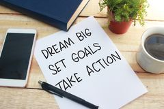 Dream Big Set Goals Take Action. Words letter, written on notepad, work desk top view. Motivational business typography quotes concept stock photography