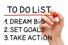 Dream Big Set Goals Take Action. Hand writing Dream Big, Set Goals, Take Action in to do list with marker on transparent wipe board Royalty Free Stock Photo