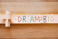 Dream big. Top view of dream big text made from colorful staples and wooden plane laying on the wood grain Stock Image