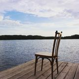 Dream. Wooden chair on a wooden pier on the river bank Royalty Free Stock Images