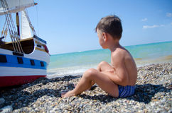 Dream boy. Little boy sitting on the beach and looking at the little ship Stock Photo