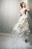 Dream Bride. Very tall Caucasian bride is posing in a dream like white wedding dress and posing against the wall Royalty Free Stock Images
