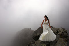 Dream of bride on mountain top in mist. Mysterious young woman in gorgeous white dress on mountain peak with fog all around Royalty Free Stock Photo