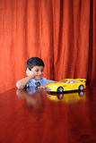 Dream car. Happy young boy with a toy car in school uniform Royalty Free Stock Photo