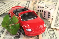 Dream car. Red car with lucky clover, dice and dollar notes Stock Photography