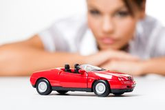 Dream car. Close-up of a toy car with thinking woman at background Stock Photography