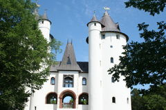 Dream castle. A white stone castle with turrets surrounded by trees Royalty Free Stock Photography